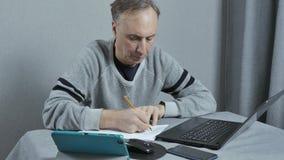 Um homem redige um plano de trabalho Trabalha em casa remotamente Usando a tecnologia moderna vídeos de arquivo