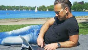 Um homem relaxa fora in fine o tempo e as ressacas no portátil filme