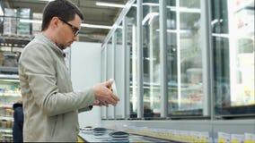 Um homem remove um frasco do iogurte do refrigerador, ele olha a etiqueta vídeos de arquivo
