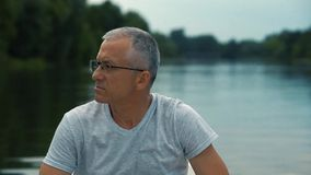 Um homem sério grisalho delgado em um t-shirt cinzento e nos vidros que enfileiram em um barco branco em um rio calmo em um verão video estoque