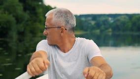 Um homem sério grisalho delgado em um t-shirt cinzento e nos vidros que enfileiram em um barco branco em um rio calmo em um verão filme
