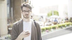 Um homem sério novo entrega os olhos do telefone celular na câmera Fotos de Stock