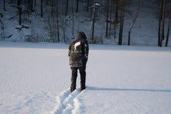 Um homem só anda na neve Silhueta dramática de um homem que anda em um esclarecimento nevado na floresta friamente imagem de stock royalty free