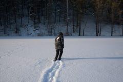 Um homem só anda na neve Silhueta dramática de um homem que anda em um esclarecimento nevado na floresta friamente fotografia de stock royalty free