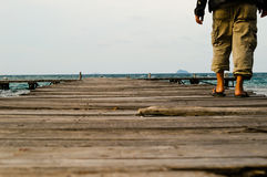 Um homem só que anda no porto de madeira Imagem de Stock Royalty Free