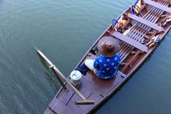 Um homem só que senta-se no barco Foto de Stock