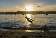 Um homem salta na lagoa em Austrália no por do sol fotografia de stock royalty free