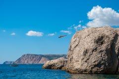 Um homem salta no mar de uma rocha imagens de stock royalty free
