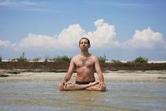 Um homem senta em terra o mar no pose dos lótus Imagens de Stock
