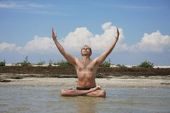 Um homem senta em terra o mar no pose dos lótus Imagem de Stock