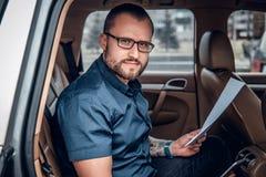 Um homem senta-se em um banco traseiro de um carro Foto de Stock Royalty Free