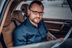 Um homem senta-se em um banco traseiro de um carro Imagens de Stock Royalty Free
