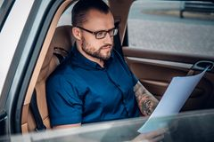 Um homem senta-se em um banco traseiro de um carro Fotografia de Stock
