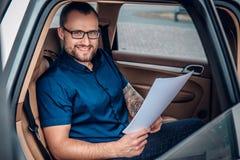 Um homem senta-se em um banco traseiro de um carro Fotos de Stock Royalty Free