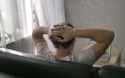 Um homem senta-se em casa no sofá e nos olhares na tela do portátil fotografia de stock