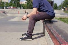 Um homem senta-se em um skate no fundo de um skatepark Os p?s fecham-se acima Conceito de Lifestile imagens de stock royalty free