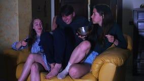 Um homem senta-se em um sofá entre duas mulheres e olha a tevê filme
