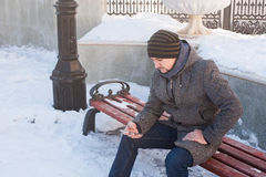 Um homem senta-se em um banco e em olhar o telefone Fotografia de Stock Royalty Free