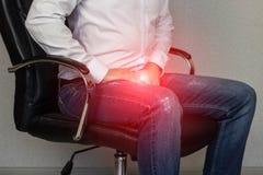 Um homem senta-se em uma cadeira do escritório e aferra-se ao virilha, gancho, prostatite fotos de stock