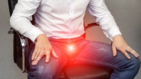 Um homem senta-se em uma cadeira do escritório, virilha dorido, gancho, prostatite, close-up imagens de stock royalty free