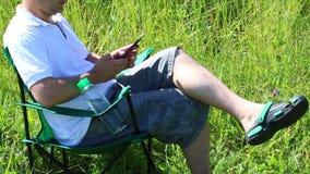 Um homem senta-se em uma cadeira do piquenique em um prado iluminado É descansar, trabalhando em um smartphone As ervas e as flor vídeos de arquivo