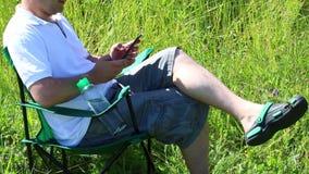 Um homem senta-se em uma cadeira do piquenique em um prado iluminado É descansar, trabalhando em um smartphone Balanço das ervas  filme