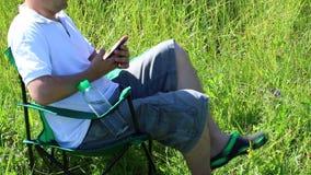 Um homem senta-se em uma cadeira do piquenique em um prado iluminado Descansa, trabalha no smartphone, a seguir nas folhas Balanç video estoque