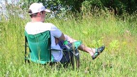 Um homem senta-se em uma cadeira do piquenique em um prado iluminado Descansar, dobra suas mãos em suas ervas da caixa e as flore filme