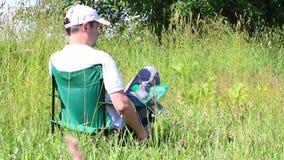 Um homem senta-se em uma cadeira do piquenique em um prado iluminado Descansar, fixa o tampão em sua cabeça Balanço das ervas e d vídeos de arquivo