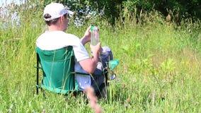 Um homem senta-se em uma cadeira do piquenique em um prado iluminado Descanso, água potável de uma garrafa Balanço das ervas e da filme