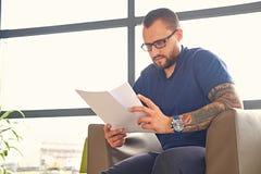 Um homem senta-se em uma cadeira e lê-se um original fotografia de stock royalty free