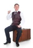 Um homem senta-se em uma mala de viagem Fotografia de Stock