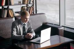 Um homem senta-se em uma tabela com um portátil Fotografia de Stock