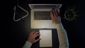 Um homem senta-se em uma tabela e tira-se um gráfico da renda em um caderno ao sentar-se em um portátil na noite 4K video estoque