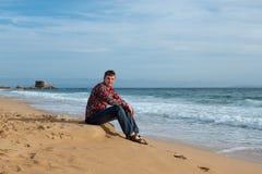 Um homem senta-se na costa do mar Fotografia de Stock