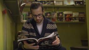 Um homem senta-se nas etapas e nas folhas através do compartimento Livrarias ou biblioteca video estoque