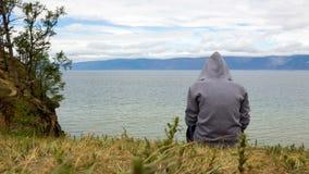 Um homem senta-se no litoral no tempo nebuloso e contempla-se 4k, lapso de tempo vídeos de arquivo