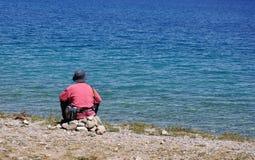 Um homem senta-se pelo lago Fotos de Stock Royalty Free