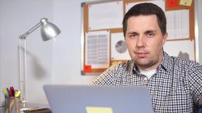 Um homem simples olha a câmera, na frente dele suportes um portátil portátil filme