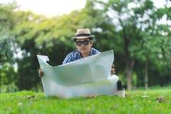 Um homem superior do viajante feliz senta-se em Forrest, abrindo um mapa imagem de stock royalty free