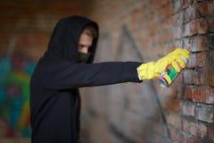 Um homem tira grafittis em uma parede de tijolo com um dossel que cobre sua cara Imagens de Stock Royalty Free