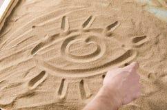 Um homem tira no símbolo da areia do olho Imagem de Stock Royalty Free
