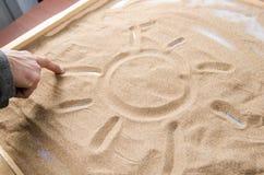 Um homem tira no símbolo da areia do sol Fotografia de Stock Royalty Free