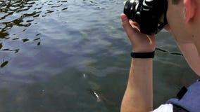Um homem toca na água, ao sentar-se em um barco video estoque