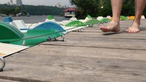 Um homem toca na água, ao sentar-se em um barco vídeos de arquivo