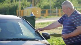 Um homem toca na quebra na janela dianteira, ele considera o custo de reparos filme