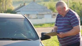 Um homem toca na quebra na janela dianteira, ele considera o custo de reparos video estoque