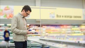 Um homem toma o alimento para fora congelado do refrigerador, ele está em um supermercado filme
