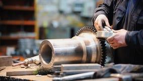 Um homem trabalha com uma engrenagem do metal em uma fábrica vídeos de arquivo