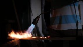 Um homem trabalha com uma tocha do gás filme